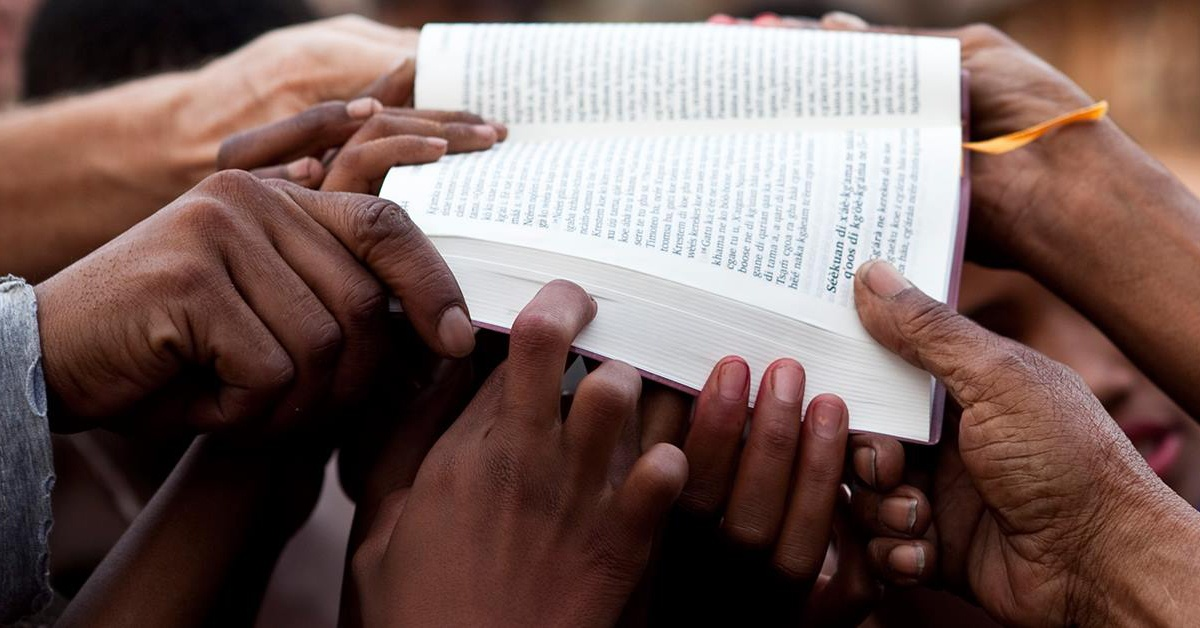 Photo of Bible held by many people